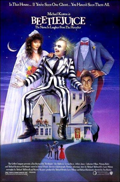 Un hombre con cara de muerto vestido con un traje a rallar blancas y negras está sentado sobre una casa. Detrás de él, un hombre y una mujer sonríen a cámara.